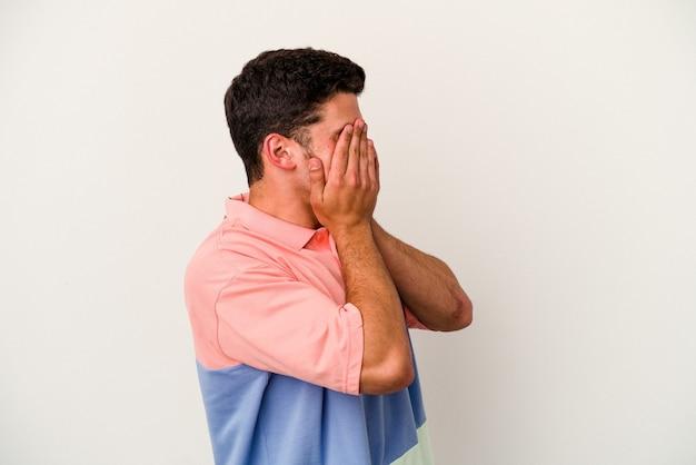 손으로 눈을 덮고 두려워 흰색 배경에 고립 된 젊은 백인 남자.