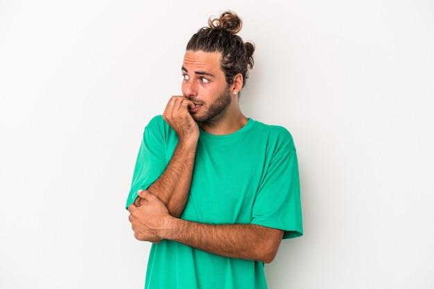 若い白人男性は、白い背景に爪を噛んで孤立し、神経質で非常に心配しています。