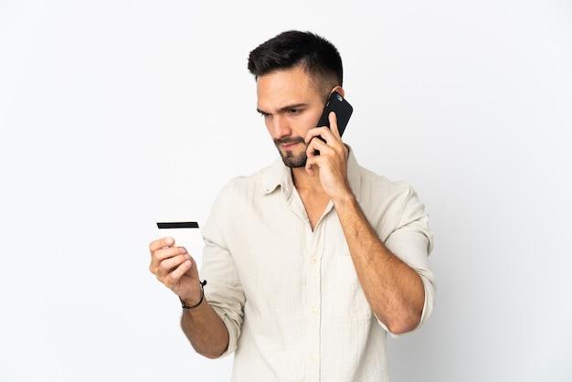 Молодой кавказский человек, изолированные на белом фоне, покупает с мобильного с помощью кредитной карты