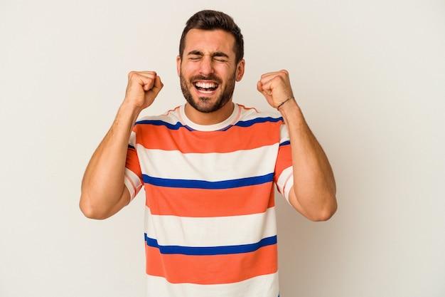 勝利、情熱、熱意、幸せな表情を祝う白い背景に分離された若い白人男性。
