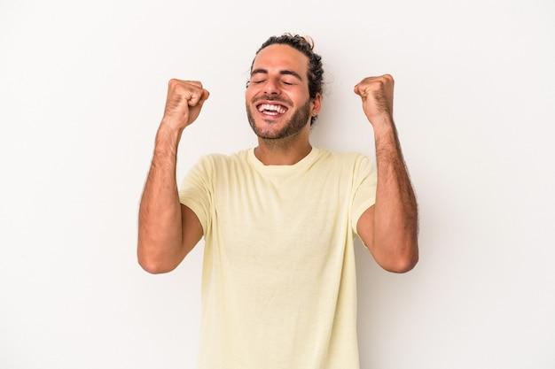 勝利、情熱と熱意、幸せな表現を祝う白い背景に孤立した若い白人男性。
