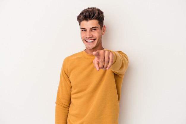 正面を指している白い背景の陽気な笑顔で孤立した若い白人男性。