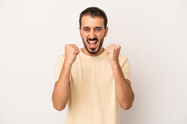 のんきと興奮して応援している白い背景で隔離の若い白人男性。利佳國際電子。