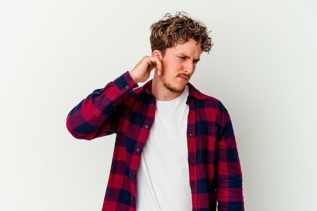 손가락으로 귀를 덮고 흰색 배경에 고립 된 젊은 백인 남자 스트레스와 큰 소리로 주변에 의해 필사적.