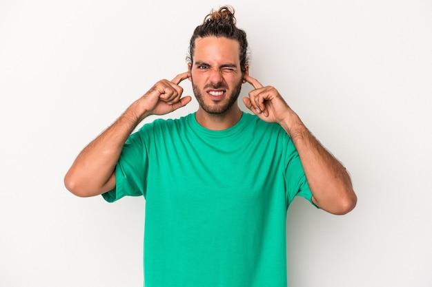 指で耳を覆っている白い背景に孤立した若い白人男性は、大声で周囲にストレスを感じ、必死になっています。