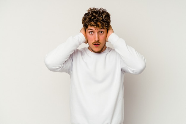 너무 시끄러운 소리를 듣지 않으려 고 손으로 귀를 덮고 흰색 배경에 고립 된 젊은 백인 남자.