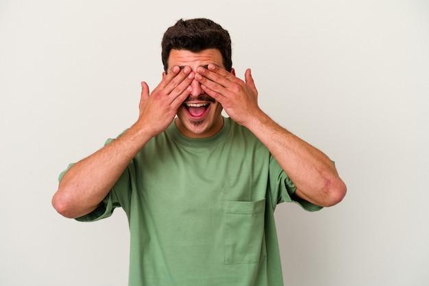 흰색 배경에 고립 된 젊은 백인 남자는 광범위 하 게 놀라움을 기다리고 미소 손으로 눈을 다루고 있습니다.