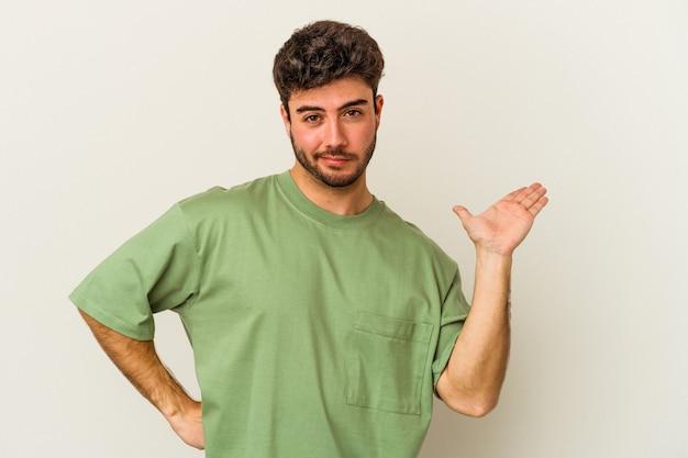 Молодой кавказский человек, изолированные на белом фоне, сомневаясь и пожимая плечами в вопросительном жесте.