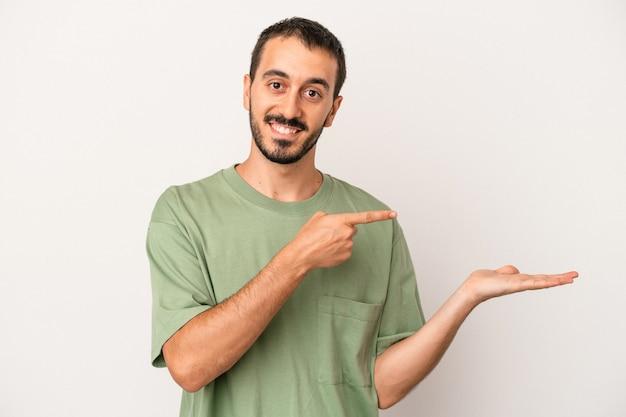 白い背景で隔離の若い白人男性は、手のひらにコピースペースを保持して興奮しました。