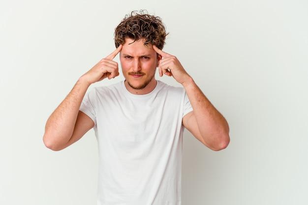 흰색 배경에 고립 된 젊은 백인 남자는 머리를 가리키는 집게 손가락을 유지하는 작업에 집중했다.