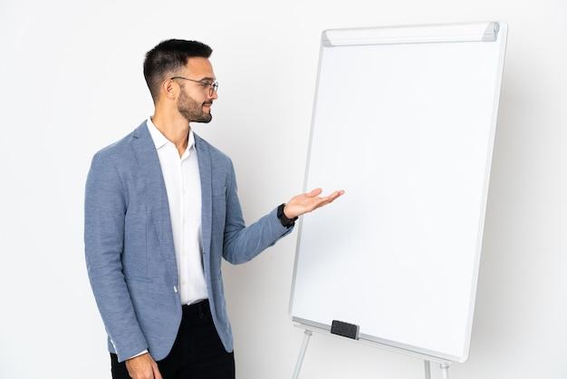 화이트 보드에 프레젠테이션을 흰색 배경에 고립 된 젊은 백인 남자