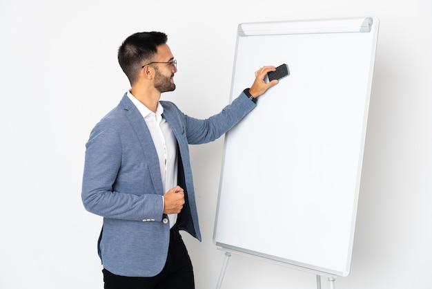 Молодой человек кавказской изолирован на белом фоне, делая презентацию на белой доске