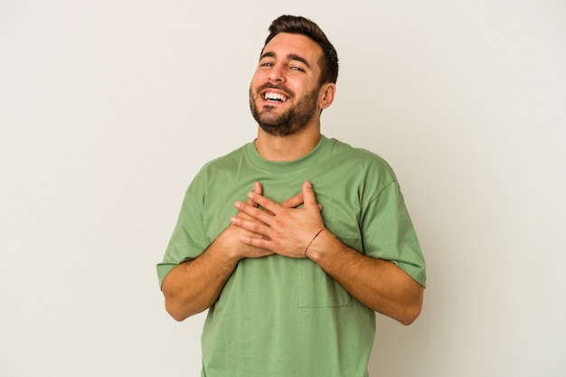 白い背景に隔離された若い白人男性は、手のひらを胸に押し付けて親しみやすい表情をしています。愛の概念。
