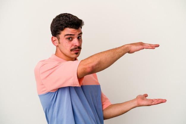 제품 프레 젠 테이 션 양손으로 뭔가 들고 흰색 배경에 고립 된 젊은 백인 남자.