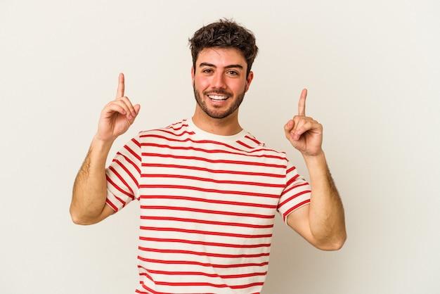 흰색 배경에 고립 된 젊은 백인 남자는 빈 공간을 보여주는 두 앞 손가락으로 나타냅니다.