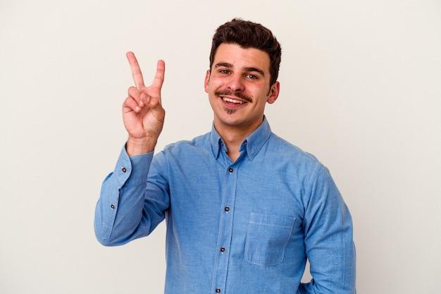 손가락으로 평화 기호를 보여주는 즐겁고 평온한 흰색 배경에 고립 된 젊은 백인 남자.