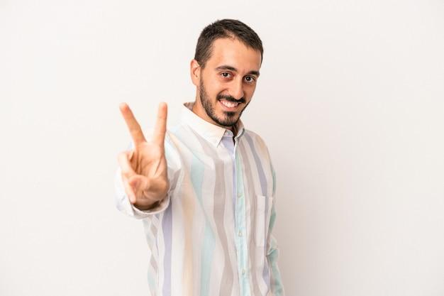 指で平和のシンボルを示す、楽しくてのんきな白い背景で隔離の若い白人男性。