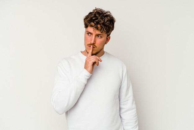 Молодой кавказский человек, изолированные на белом фоне, храня в секрете или прося молчания.