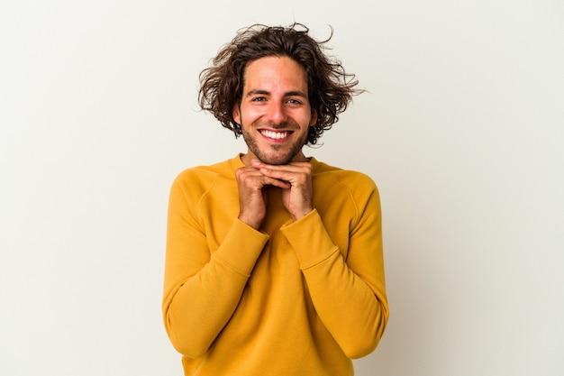Молодой человек кавказской, изолированные на белом фоне держит руки под подбородком, счастливо смотрит в сторону.