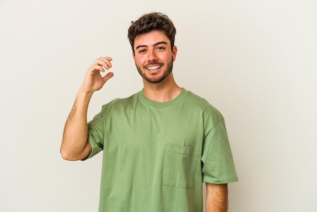 뭔가 대해 웃 고, 손으로 입을 덮고 흰색 배경에 고립 된 젊은 백인 남자.