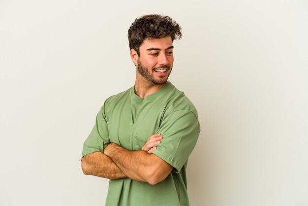 笑いと楽しい時を過す白い背景に分離された若い白人男性。