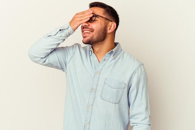 白い背景に分離された若い白人男性は、頭に手を当ててうれしそうに笑います。幸福のコンセプト。