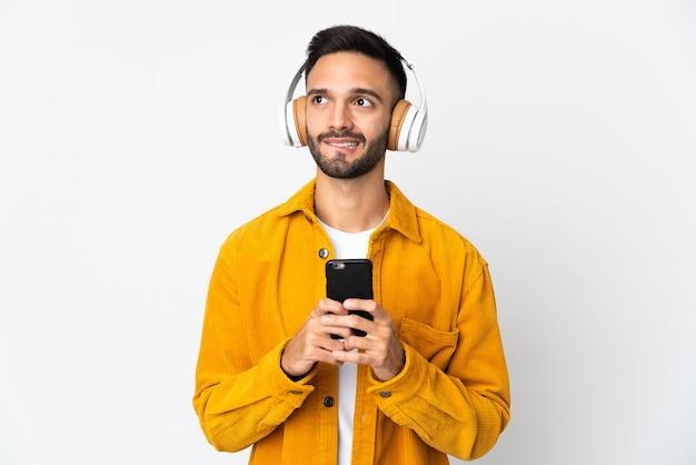 携帯電話で音楽を聴いて考えて白い背景で隔離の若い白人男性