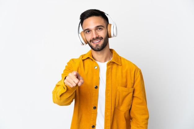 音楽を聴いて白い背景で隔離の若い白人男性
