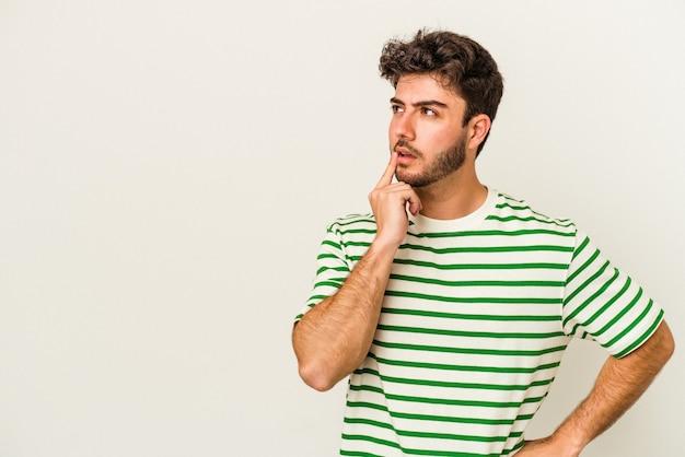 Молодой человек кавказской изолирован на белом фоне, глядя в сторону с сомнительным и скептическим выражением лица.