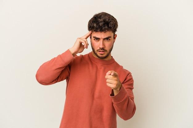 Молодой человек кавказской изолирован на белом фоне указывая храм пальцем, думая, сосредоточился на задаче.