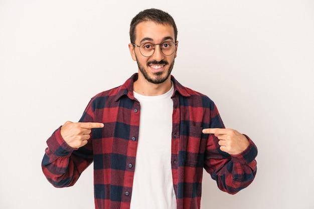 白い背景で隔離の若い白人男性は、指で下向き、前向きな気持ちです。
