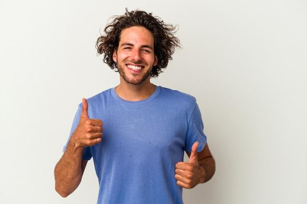 笑顔と自信を持って、両方の親指を上げて白い背景で隔離の若い白人男性。