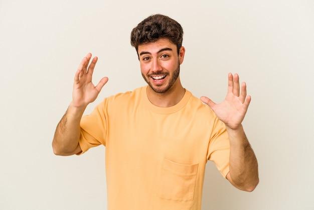 즐거운 놀라움을 받고 흥분 하 고 손을 올리는 흰색 배경에 고립 된 젊은 백인 남자.