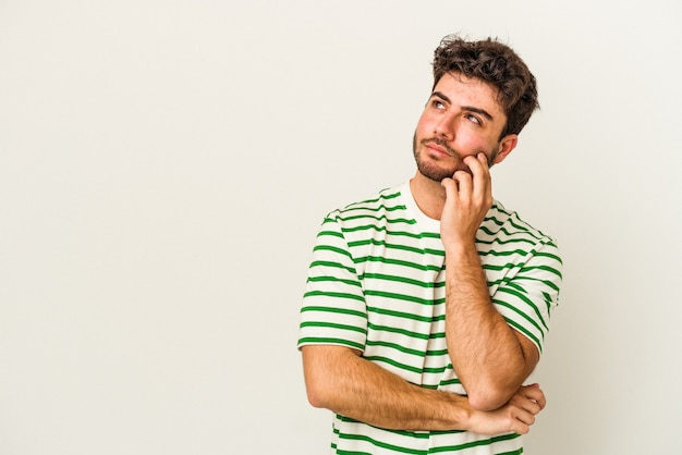 Молодой человек кавказской, изолированные на белом фоне, расслабился, думая о чем-то, глядя на копию пространства.