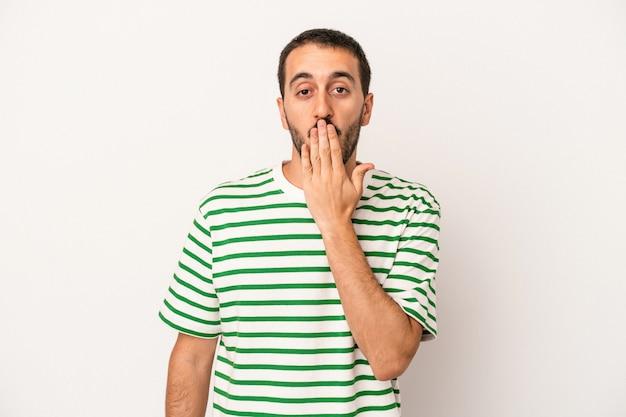 白い背景に孤立した若い白人男性はショックを受け、手で口を覆い、何か新しいものを発見することを切望していました。