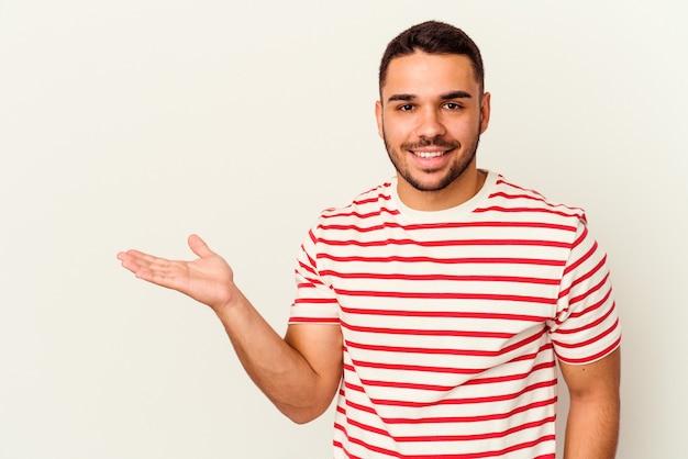手のひらにコピー スペースを表示し、腰に別の手を保持している白い背景に分離された若い白人男性。