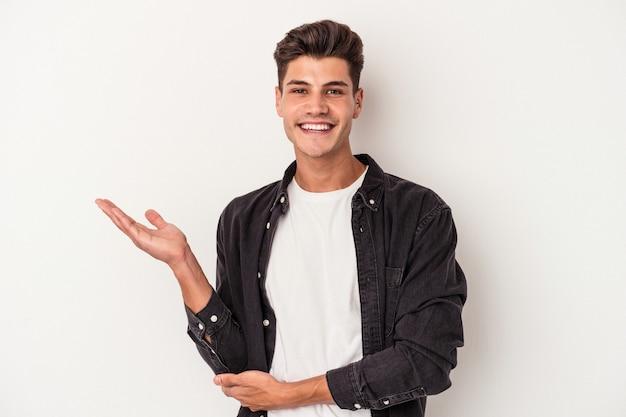 手のひらにコピースペースを示し、腰に別の手を保持している白い背景で隔離の若い白人男性。