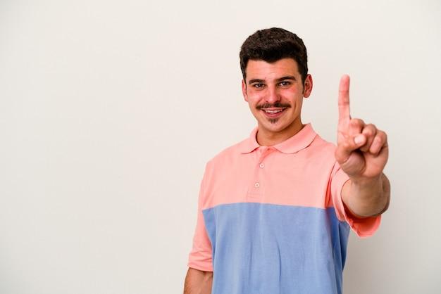 손가락으로 번호 하나를 보여주는 흰색 배경에 고립 된 젊은 백인 남자.
