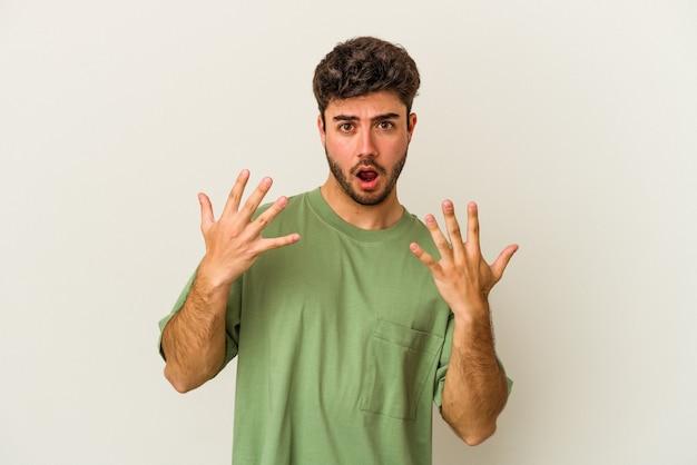 若い白人男性は、手で 10 番を示す白い背景に分離されました。