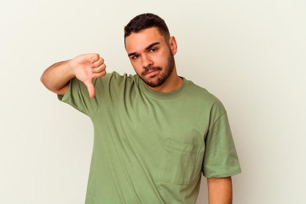 親指を下にして、失望の概念を示す白い背景に分離された若い白人男性。