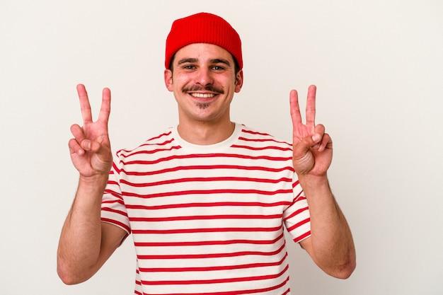승리 기호를 표시 하 고 광범위 하 게 웃 고 흰색 배경에 고립 된 젊은 백인 남자.