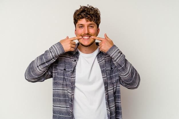 입에서 손가락을 가리키는 흰색 배경 미소에 고립 된 젊은 백인 남자.