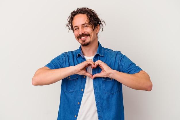 웃 고 손으로 심장 모양을 보여주는 흰색 배경에 고립 된 젊은 백인 남자.