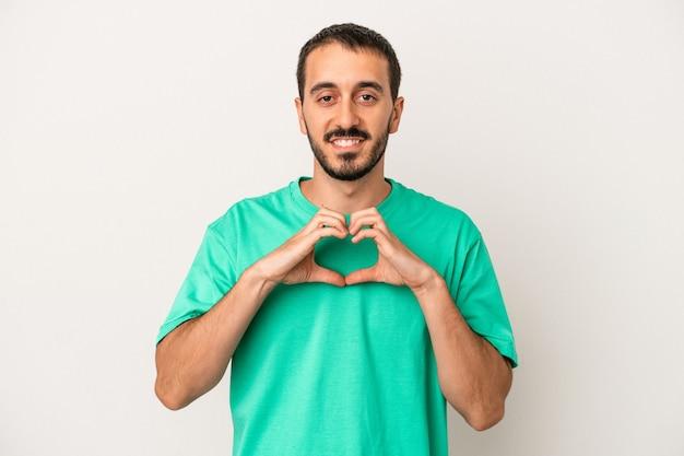 笑顔と手でハートの形を示す白い背景で隔離の若い白人男性。