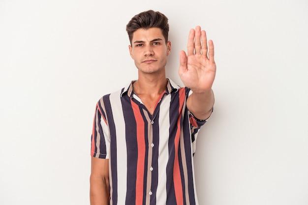白い背景に孤立した若い白人男性は、一時停止の標識を示している手を伸ばして立って、あなたを妨げています。