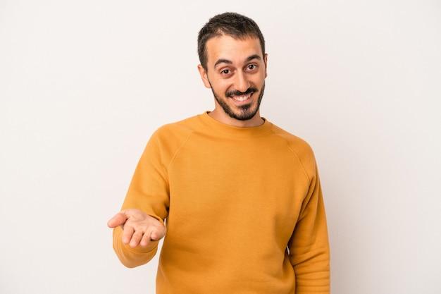挨拶のジェスチャーでカメラに手を伸ばして白い背景で隔離の若い白人男性。