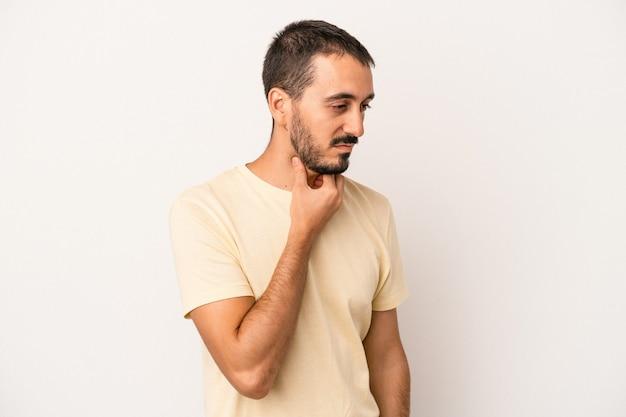 白い背景で隔離の若い白人男性は、ウイルスや感染症のために喉の痛みに苦しんでいます。