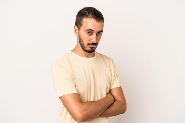 Молодой человек кавказской изолирован на белом фоне подозрительно, неуверенно, исследует вас.