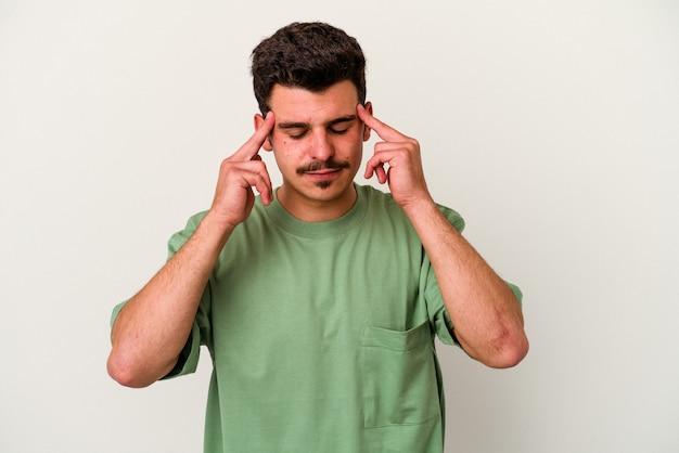 Молодой кавказский человек, изолированные на белом фоне, трогательно виски и головная боль.