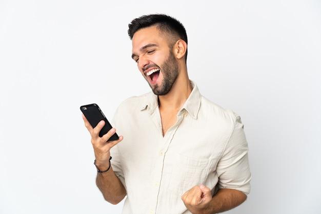 Молодой кавказский человек изолирован на белом фоне с помощью мобильного телефона и делает жест победы